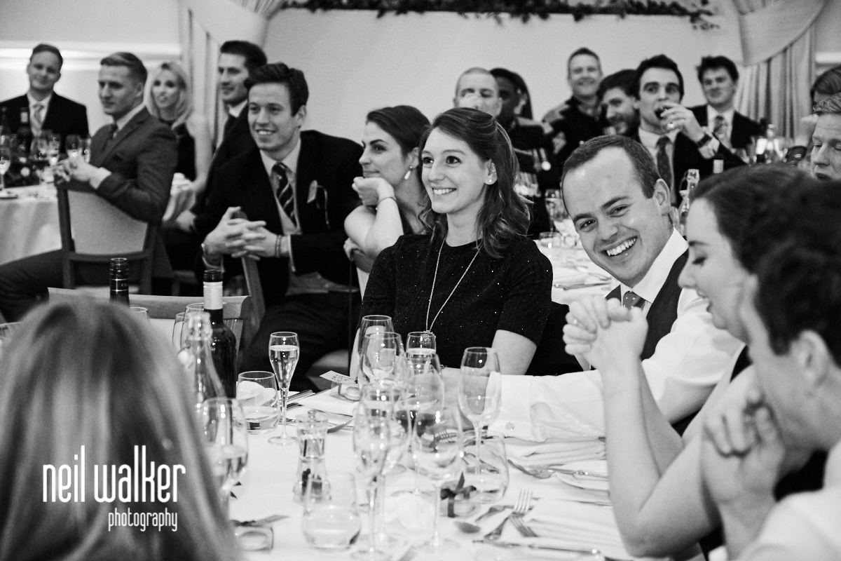 guests laughing and looking at each other during the best man's speech