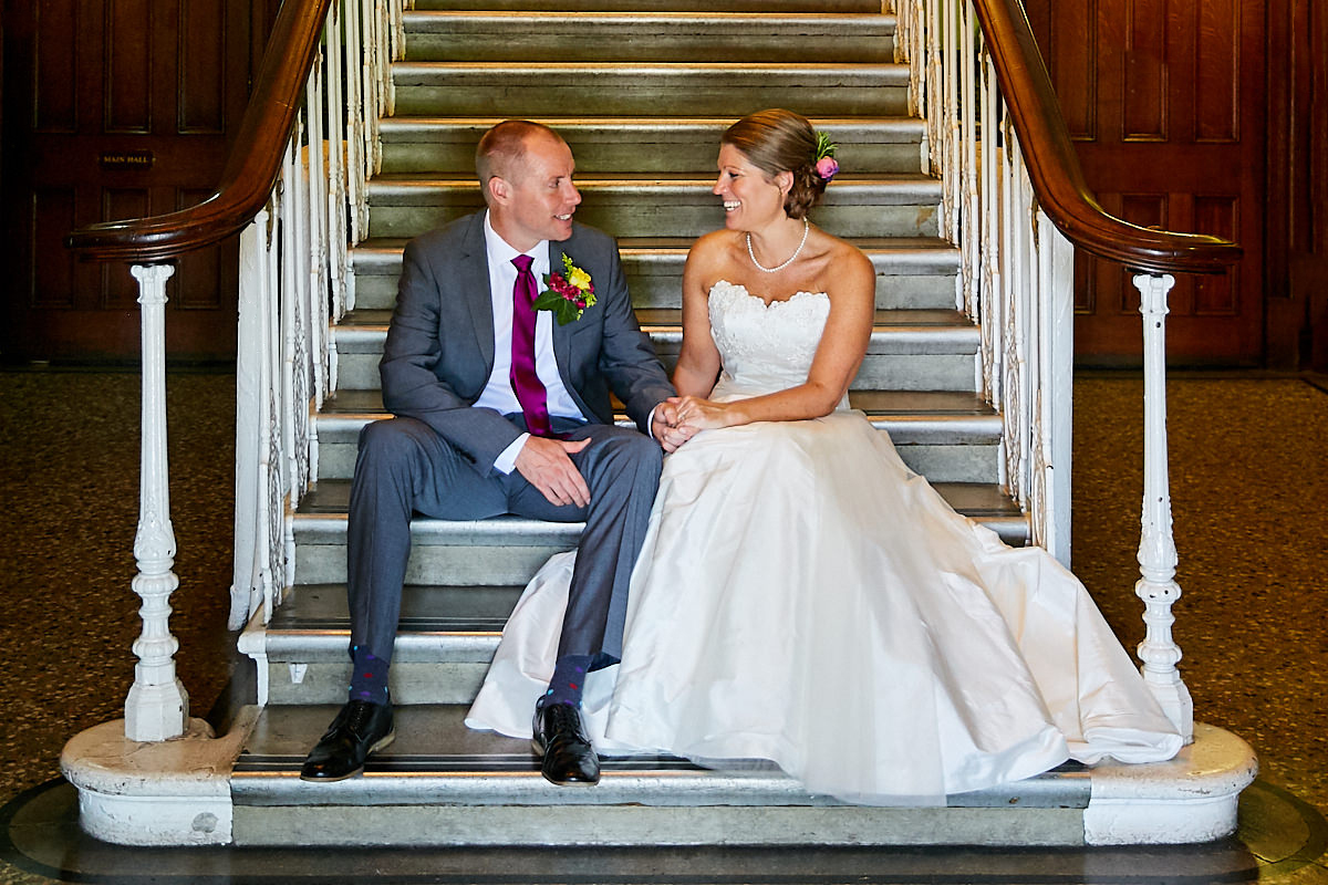 a bride and groom sitting on stairs after their wedding ceremony