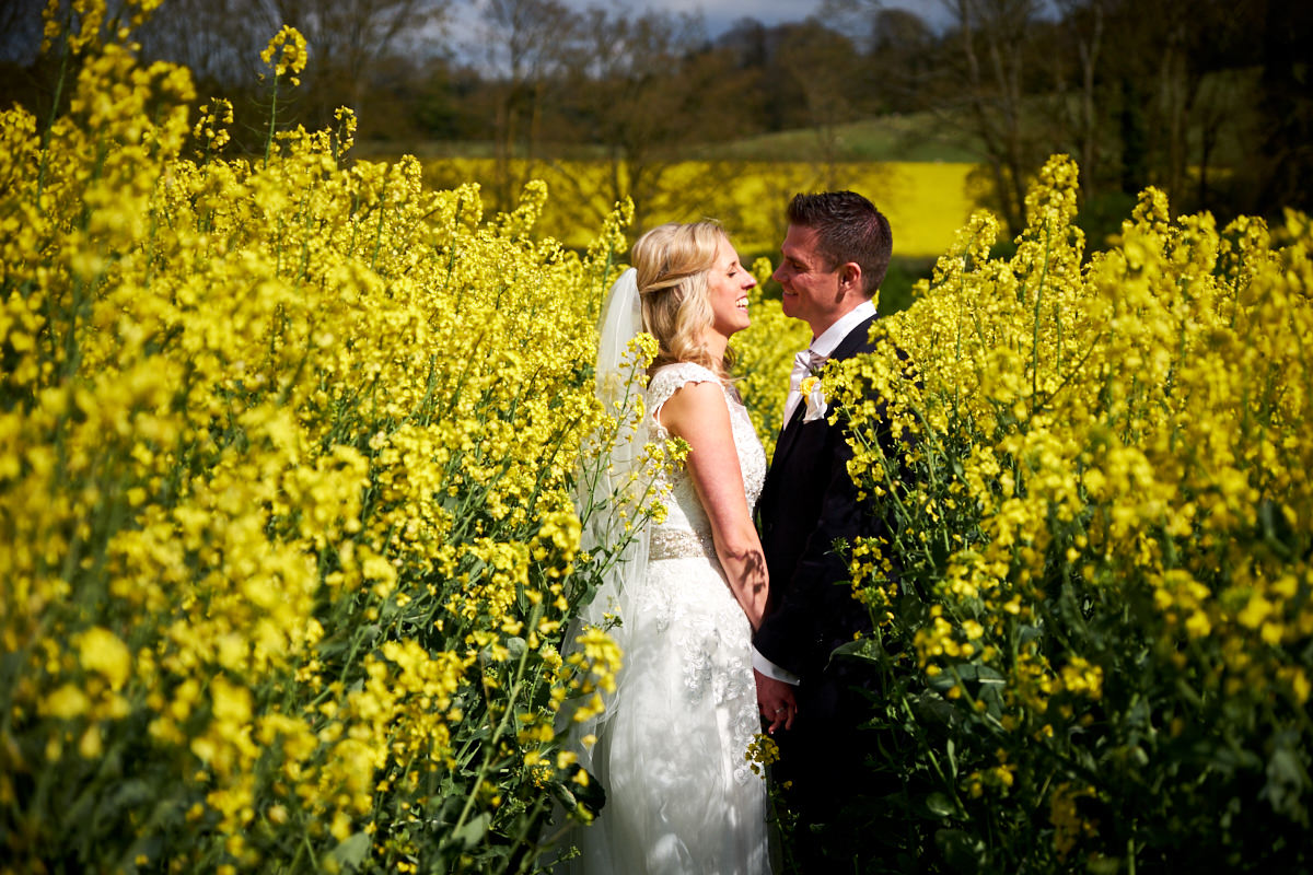 a bride and groom looking at each other lovingly in a field in Sussex