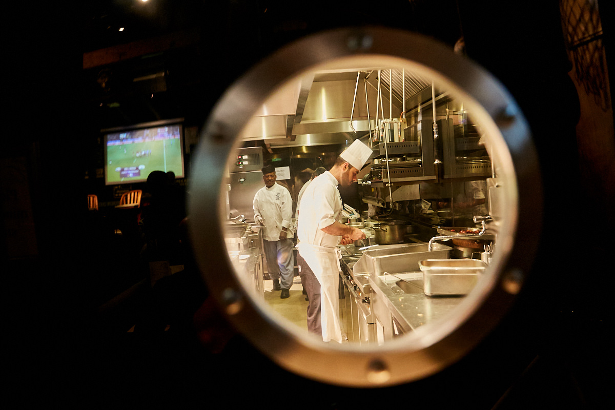 a chef working in his kitchen photographed through a window