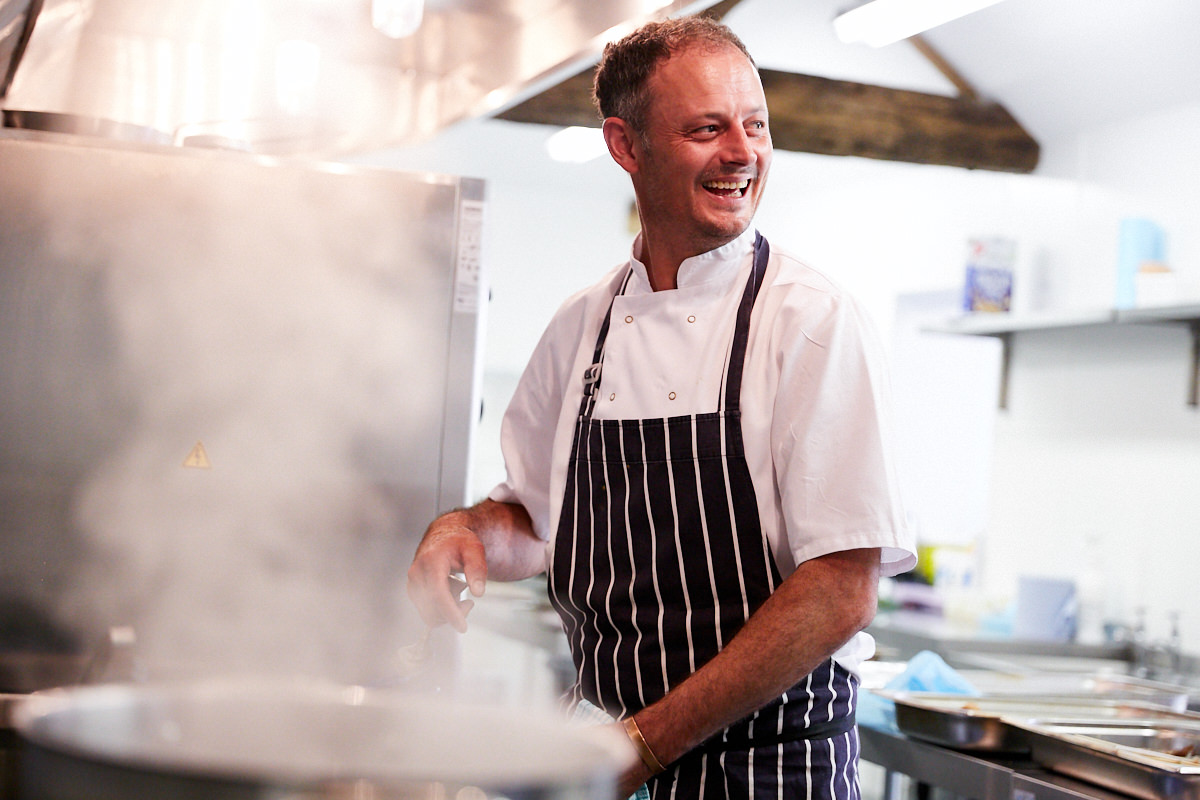a chef laughing while he cooks at an event in West Sussex