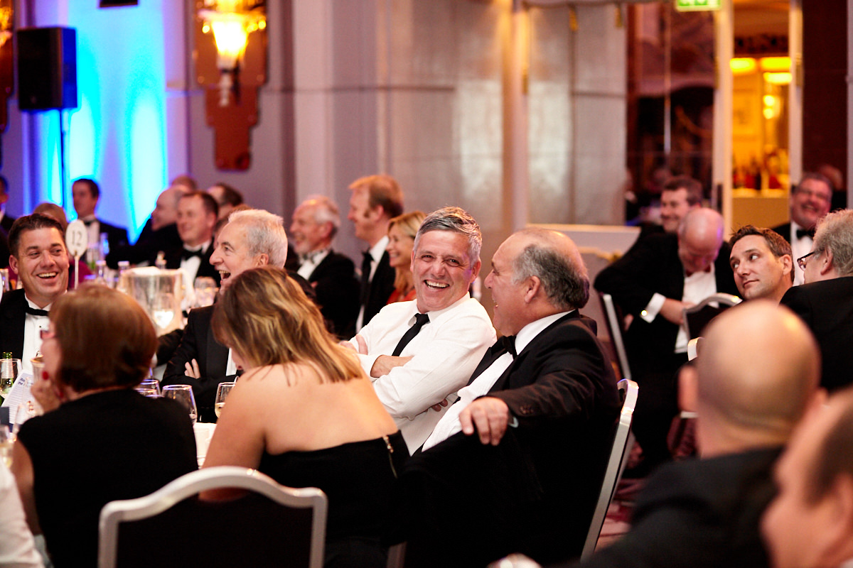 a guest talking to another guest on his table at an event at The Sheraton Grand London Park Lane