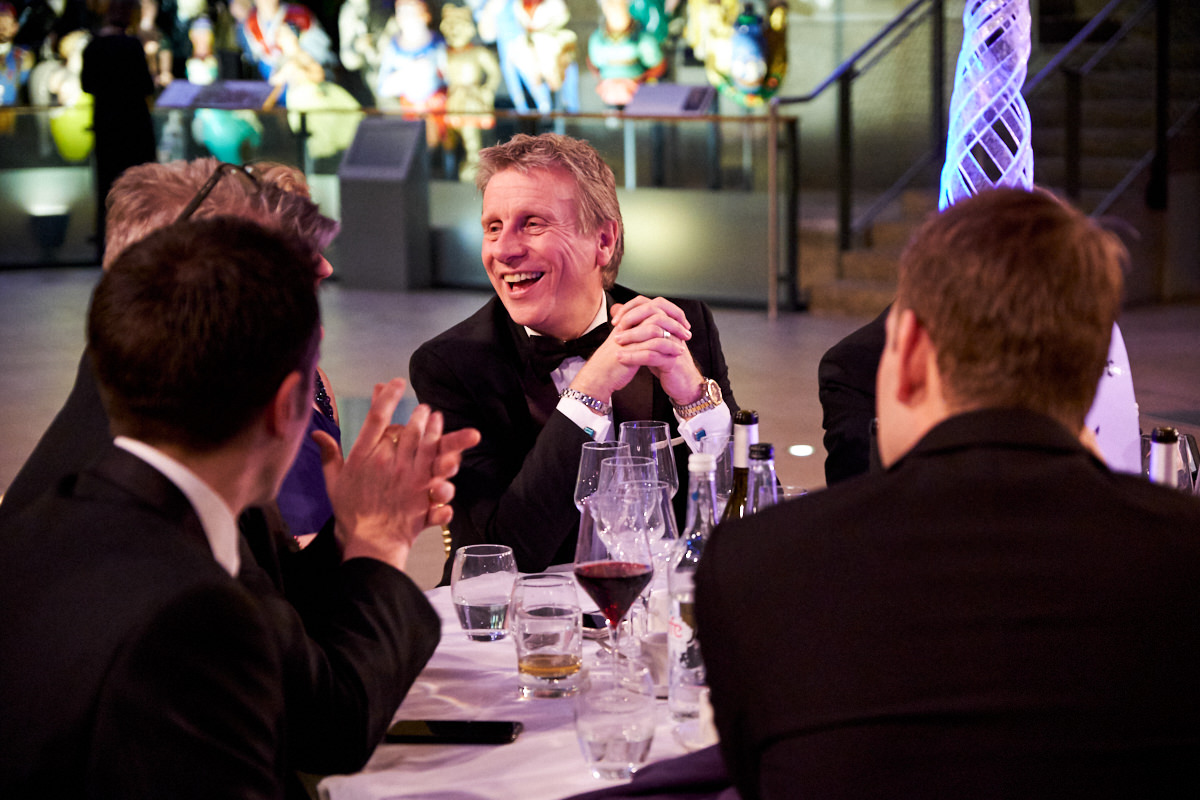 a guest laughing with another guest next to him at a table at an event