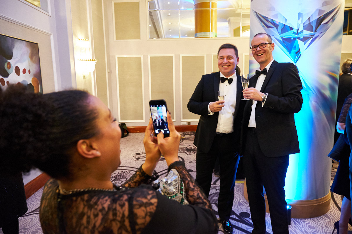 a guest taking a photograph of other guests at an event at The Hilton Park Lane