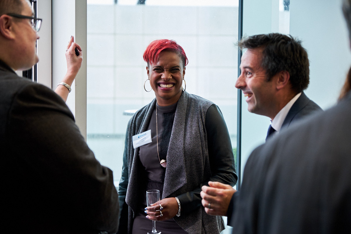 a lady at an event in London laughing at a joke