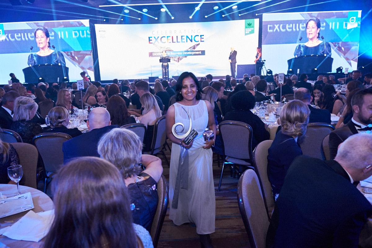 an award winner walks back to her seat after receiving her award