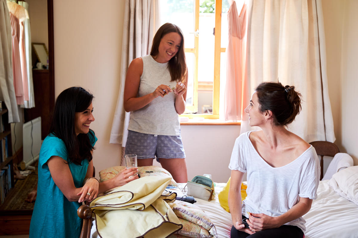 the bride and bridesmaids talking while they get ready for her wedding