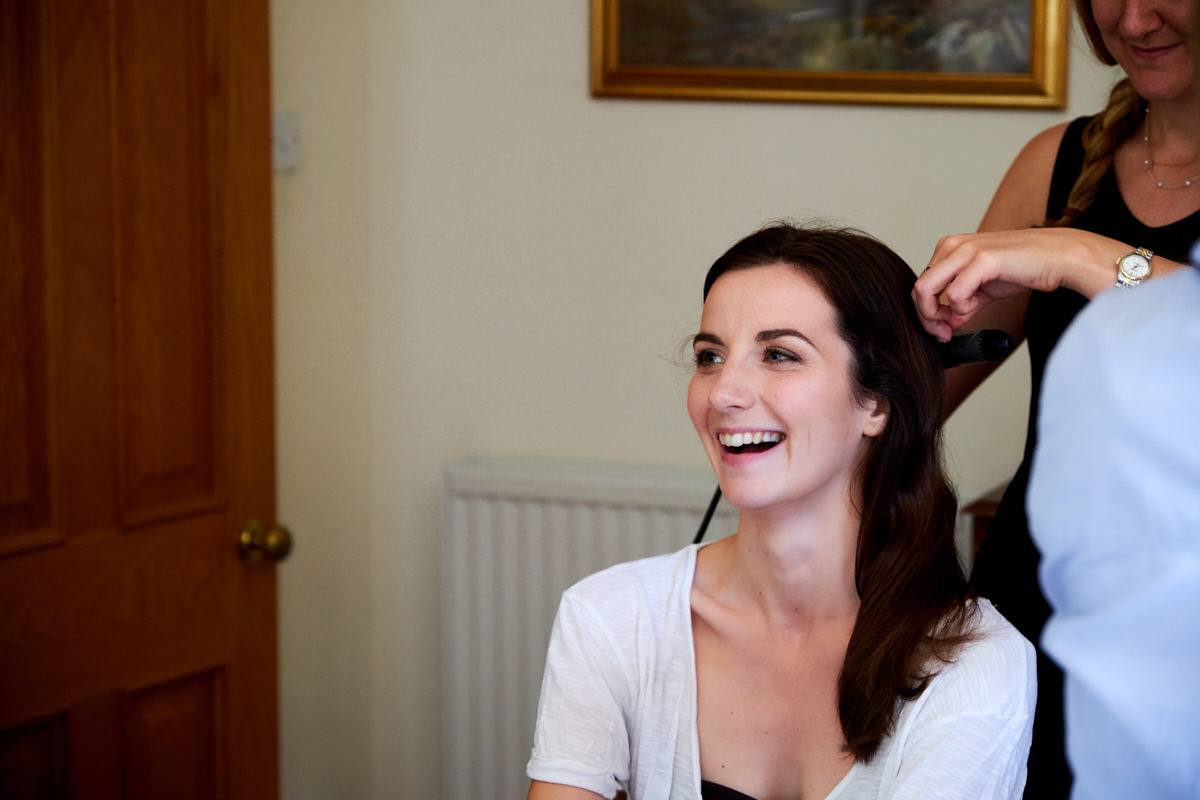 the bride laughing while she has her hair done for her Sussex marquee wedding