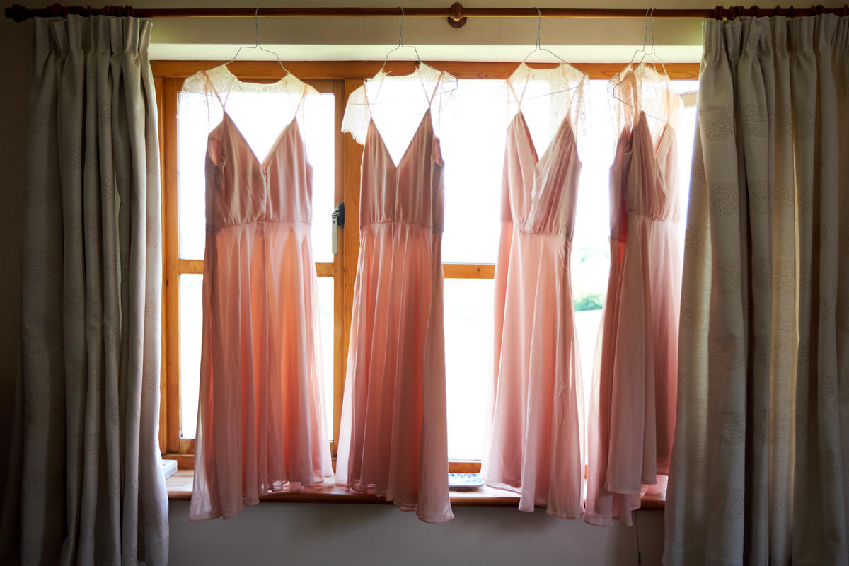 the bridesmaids dresses hanging in the window