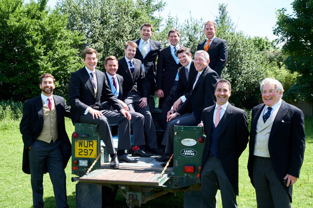the groom and groomsmen posing in the back of a landrover