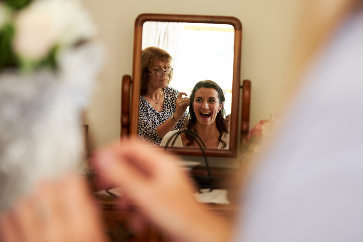 a photo of the bride laughing in a mirror