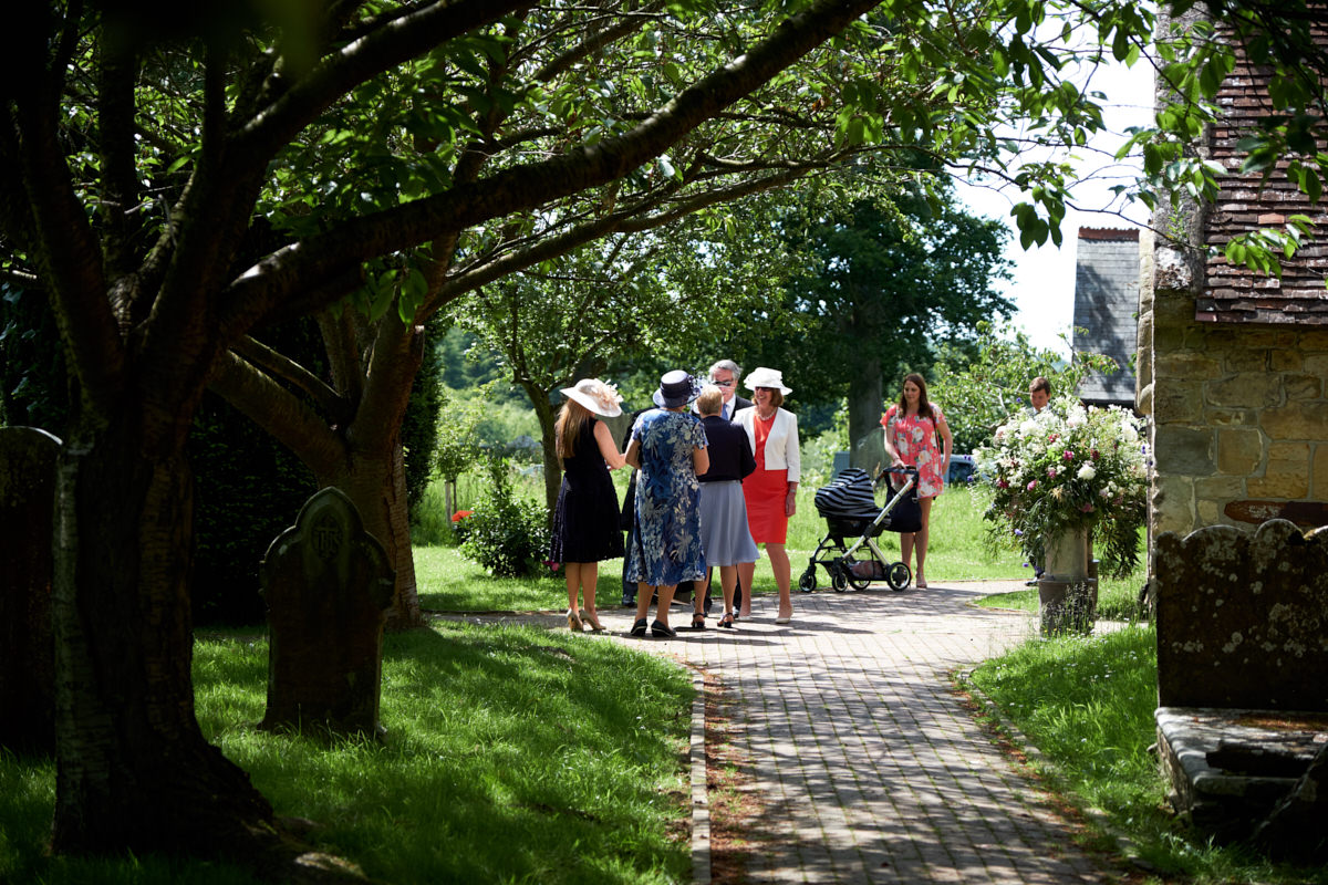 guests gathering outside the church at a Sussex wedding