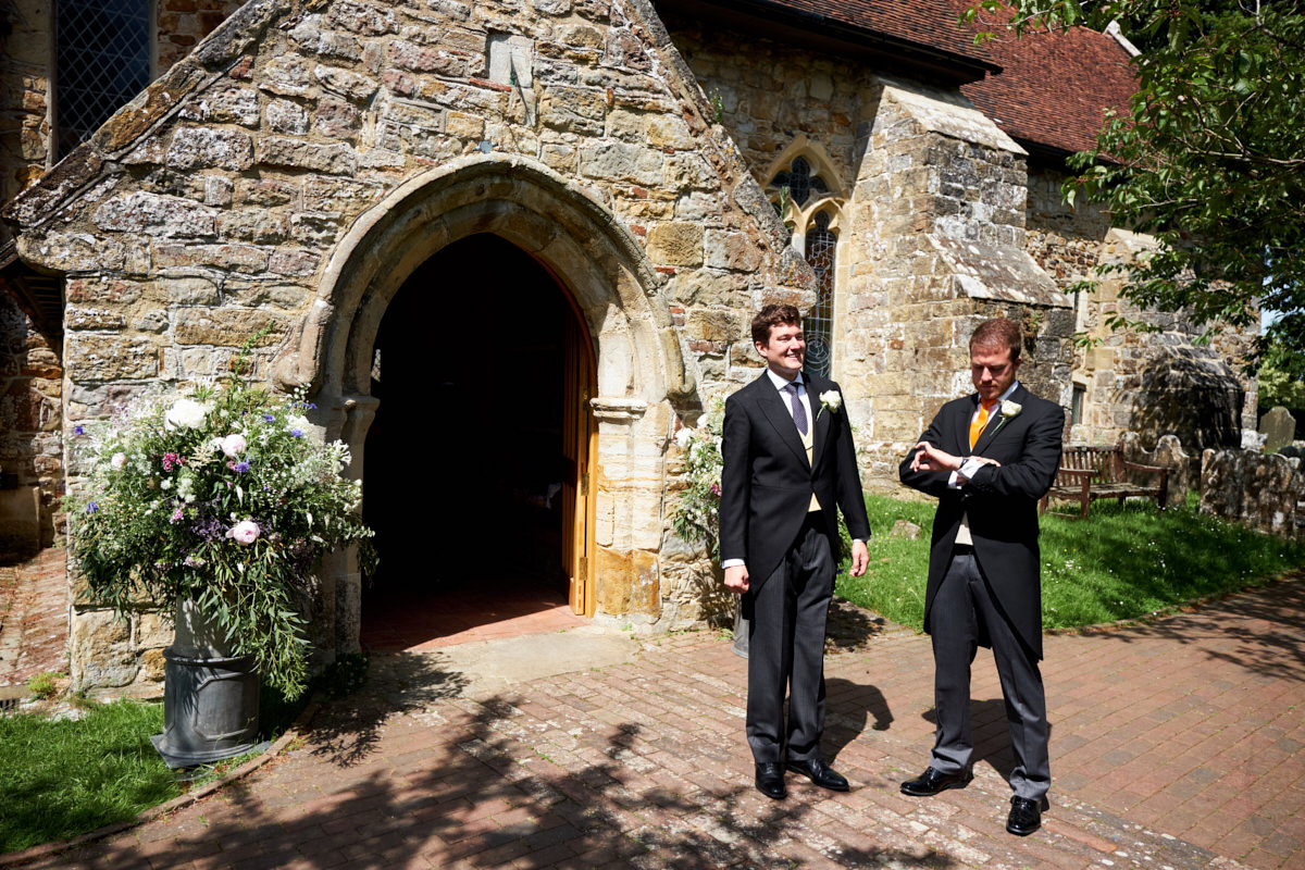 an usher looks at his watch as he and the groom wait for guests outside the church