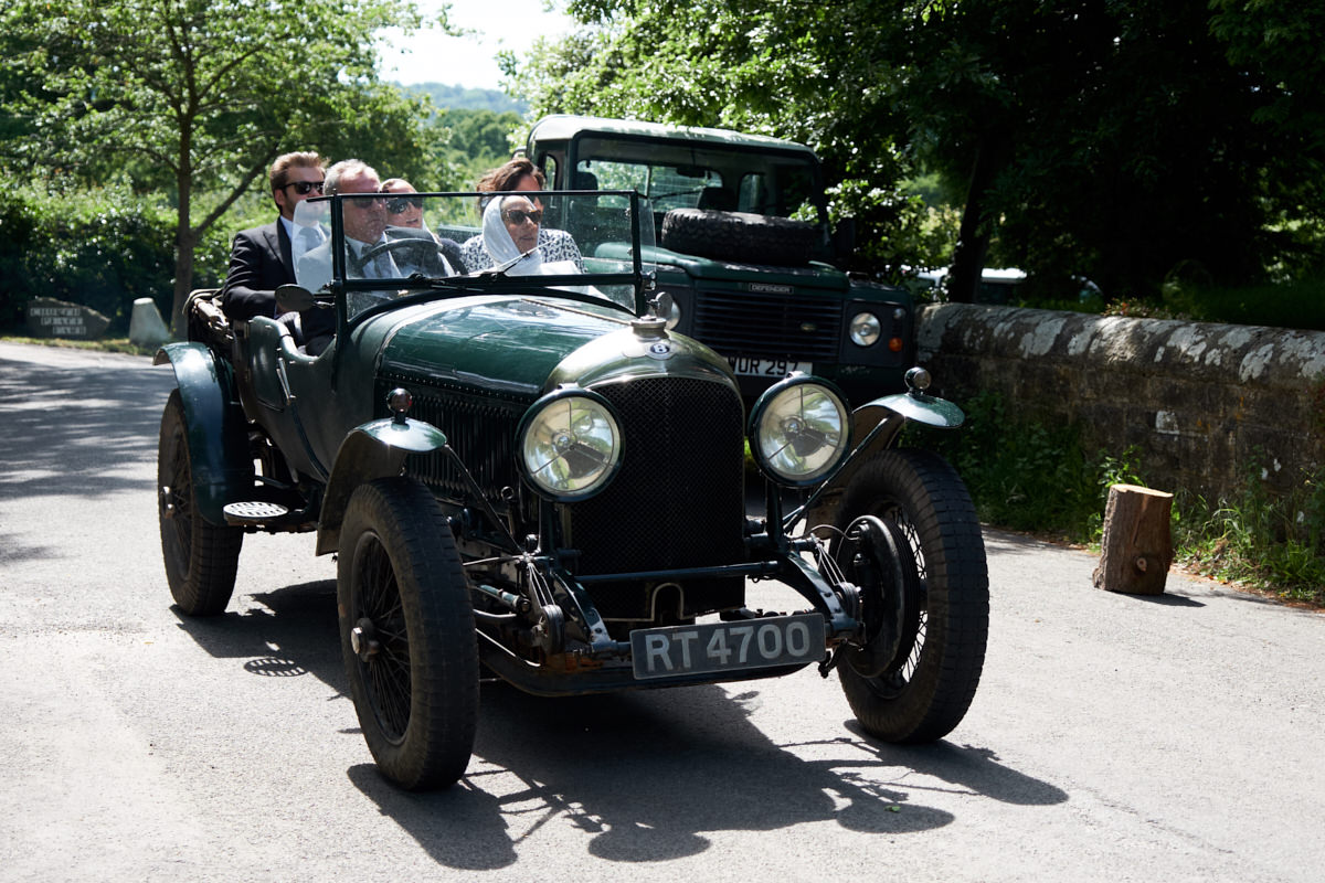 guests arriving for this Sussex wedding in vintage wedding cars