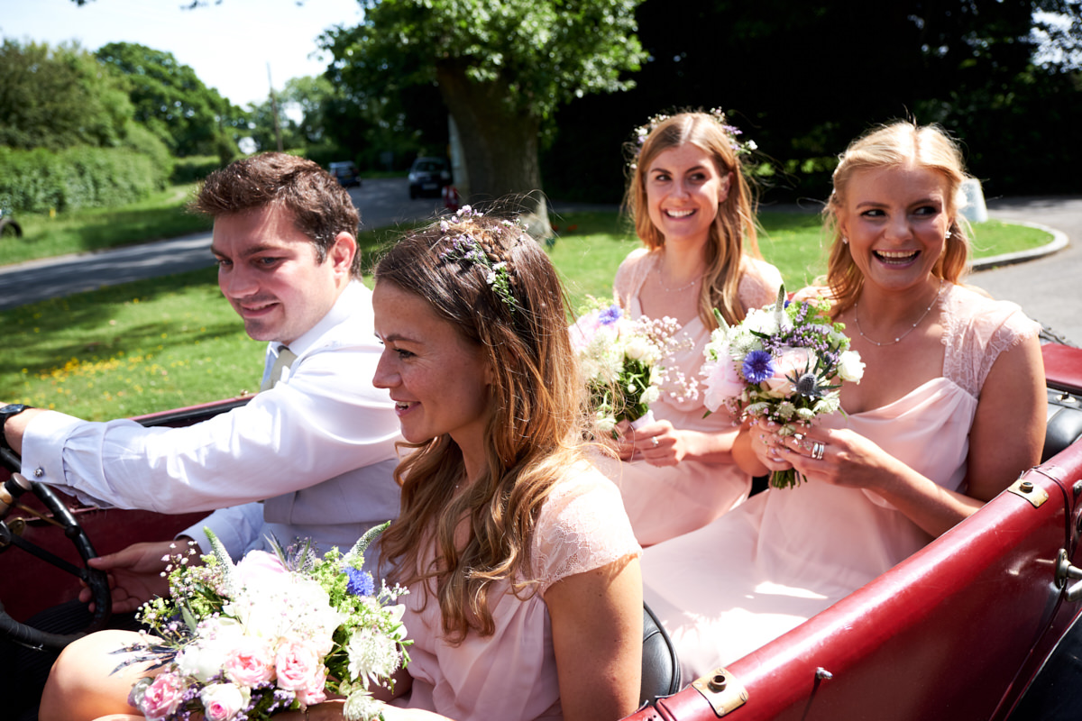 the bridesmaids arrive at the church in a vintage wedding car