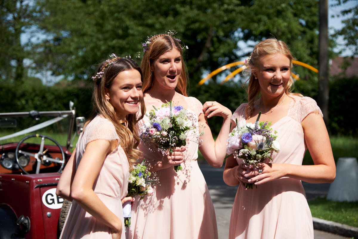 bridesmaids smiling as they arrive at the church