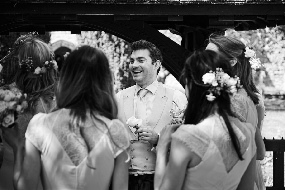 the bride's brother laughing with the bridesmaids