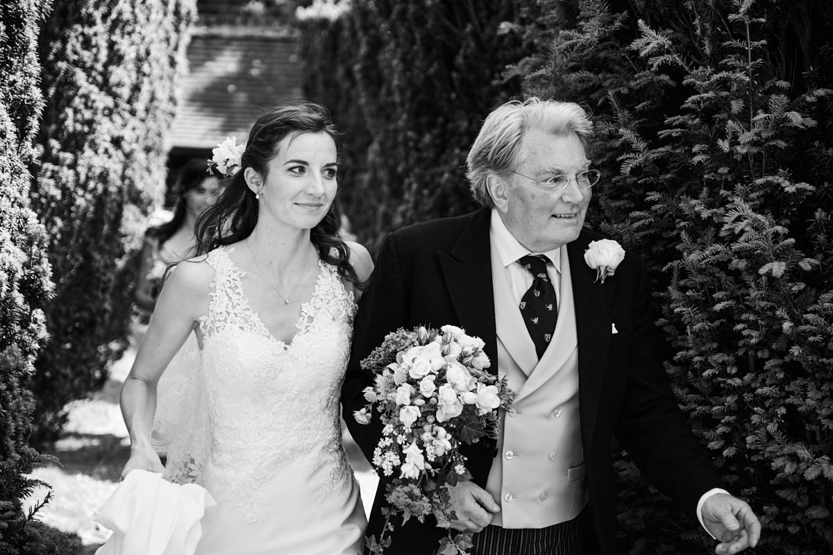 the bride and her father walking to the entrance to the church at her Sussex wedding