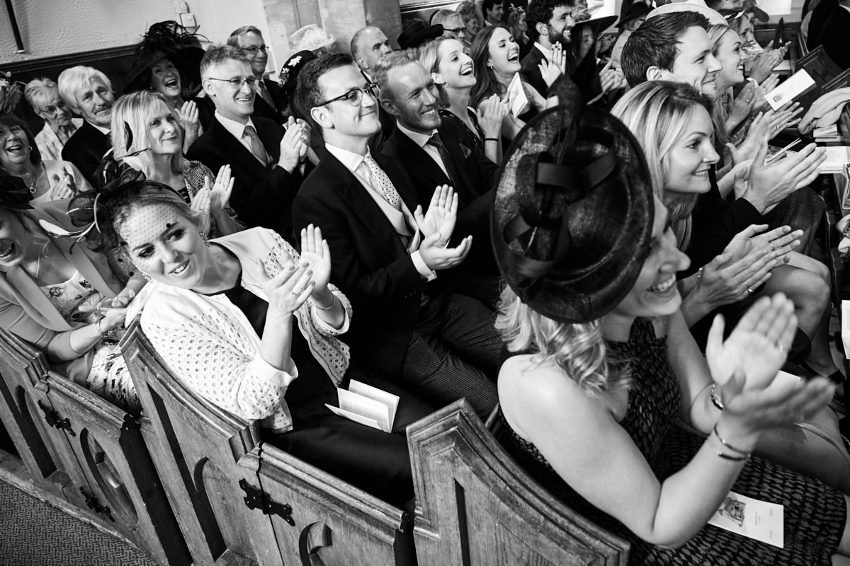 guests clapping while the married couple kiss at this Sussex wedding