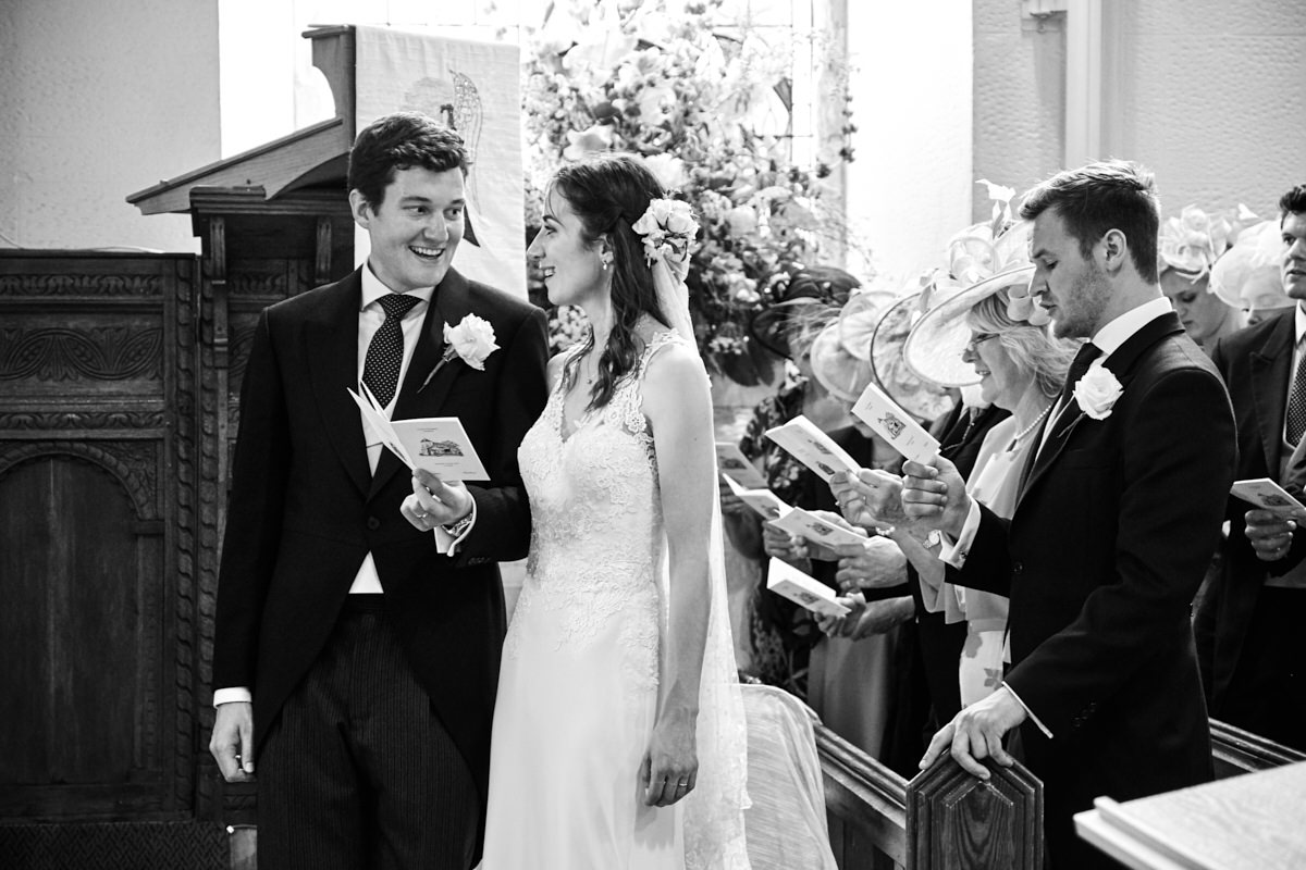 the bride and groom smile at each other while they sing a hymn