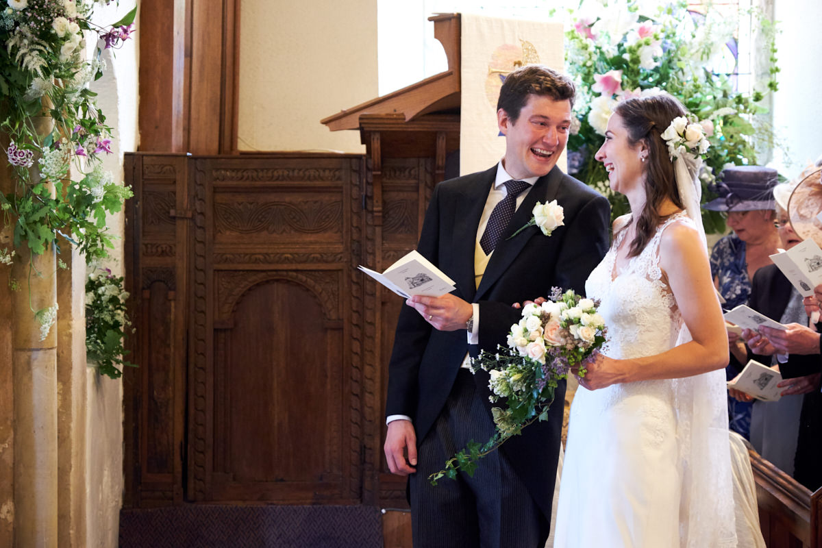 the bride and groom singing a hymn as they laugh