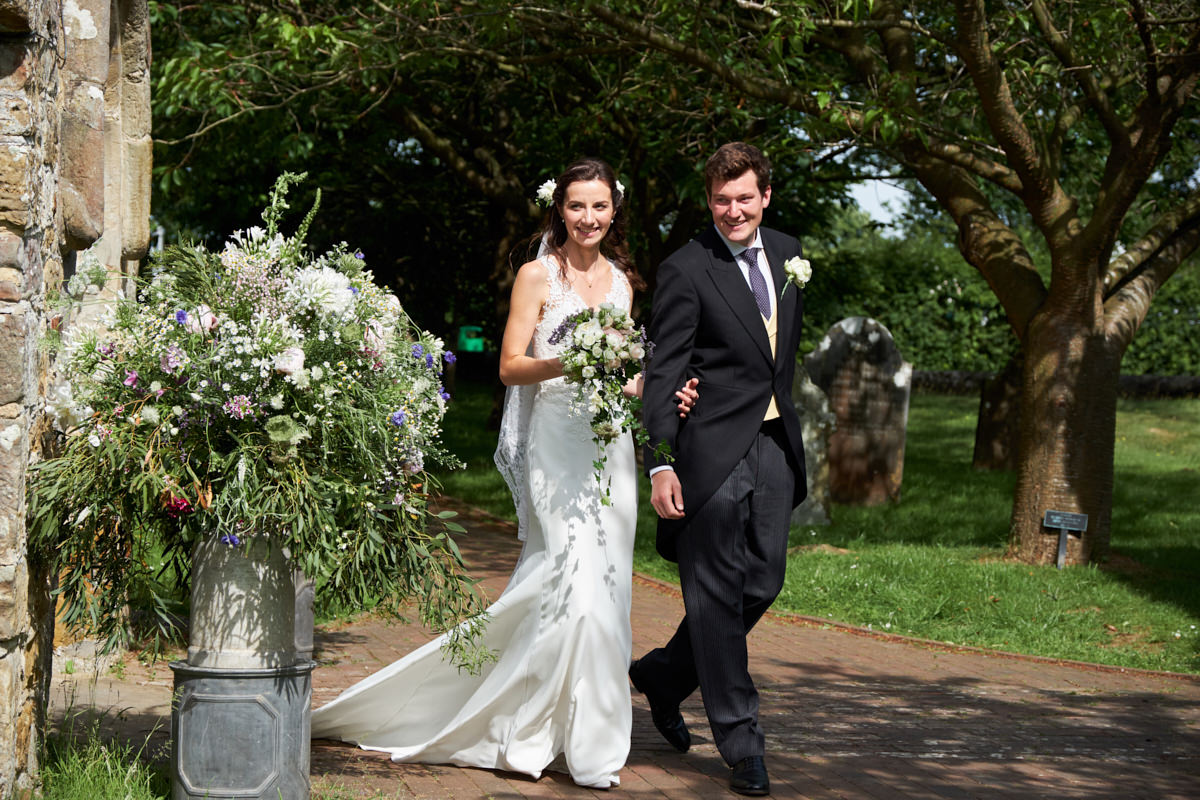 the bride and groom walk out of the church together into the sun