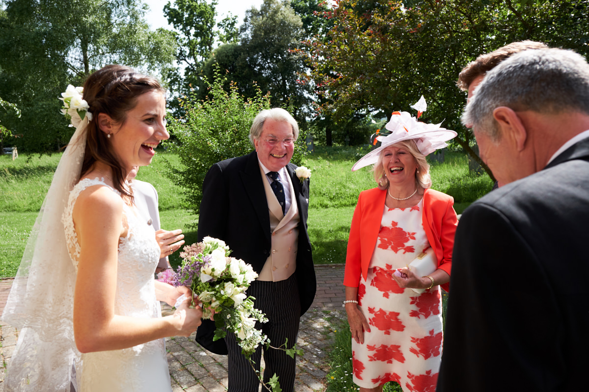 the bride and groom laugh with her father and his mother outside the church