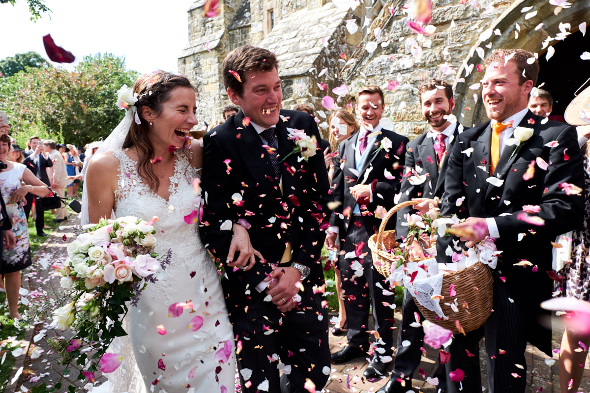 the bride and groom react to having confetti thrown at them