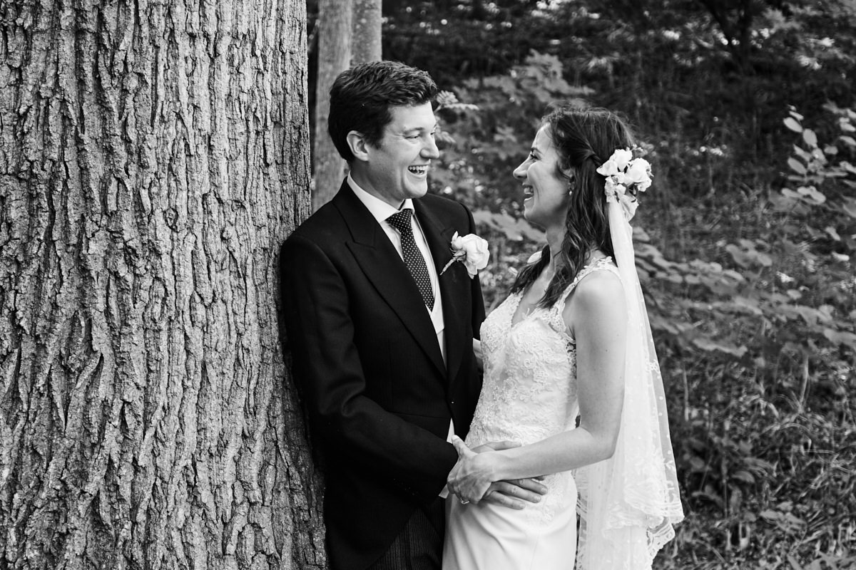 the bride and groom laugh together standing by a tree in a Sussex field