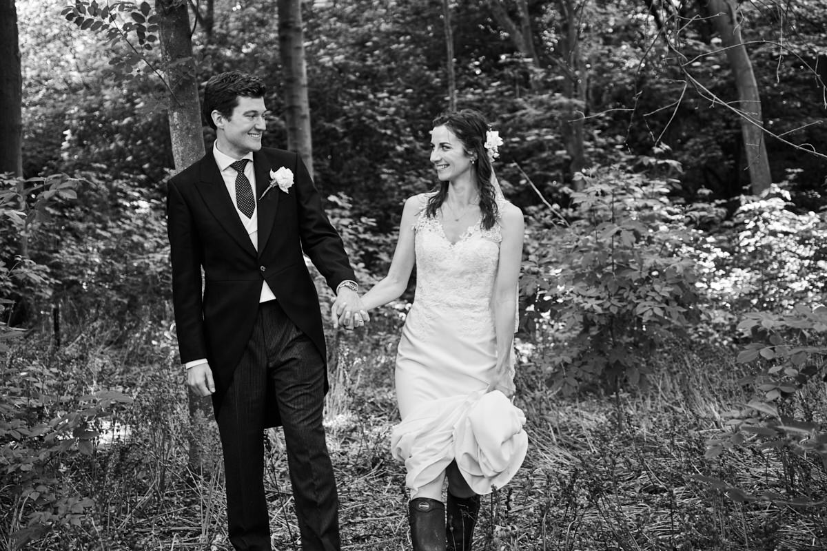 the bride and groom walking through a Sussex field