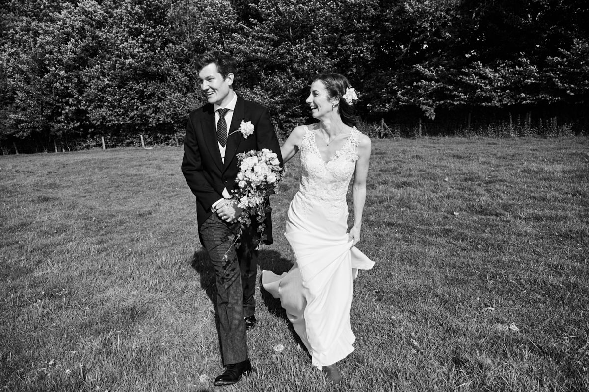 the bride and groom laughing as they walk across a Sussex field to their marquee wedding in front of their guests