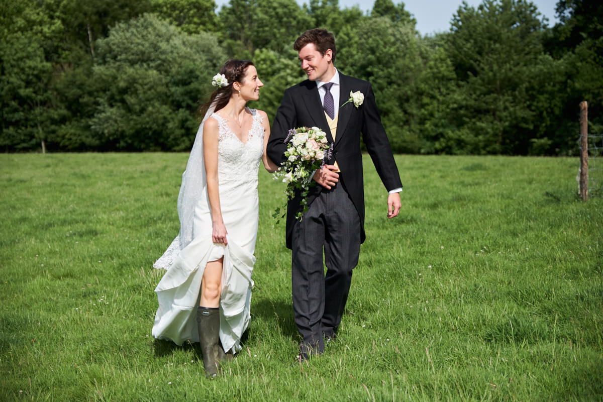 the bride and groom wearing boots as they cross a Sussex field