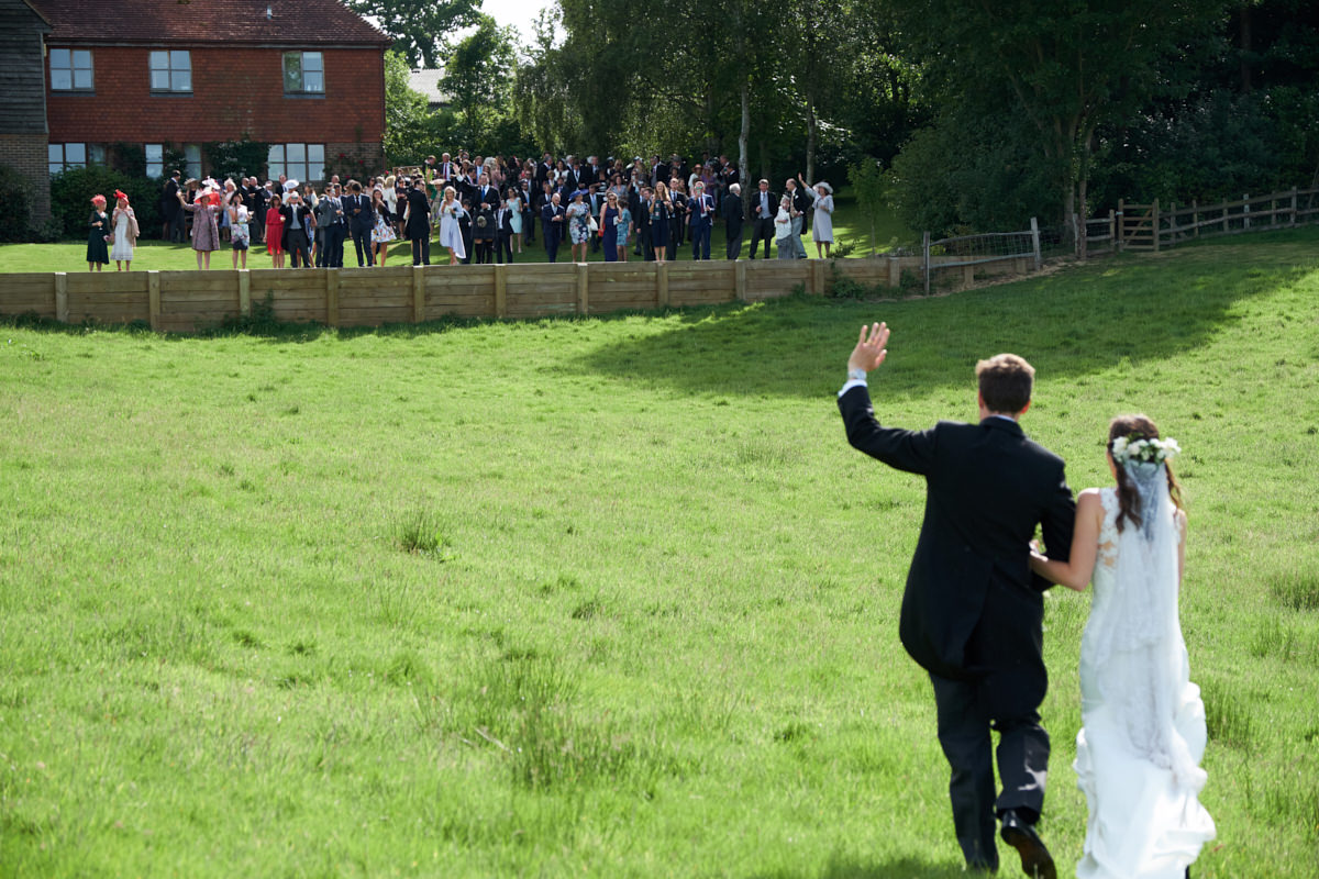 guests cheer as the bride and groom walk towards them
