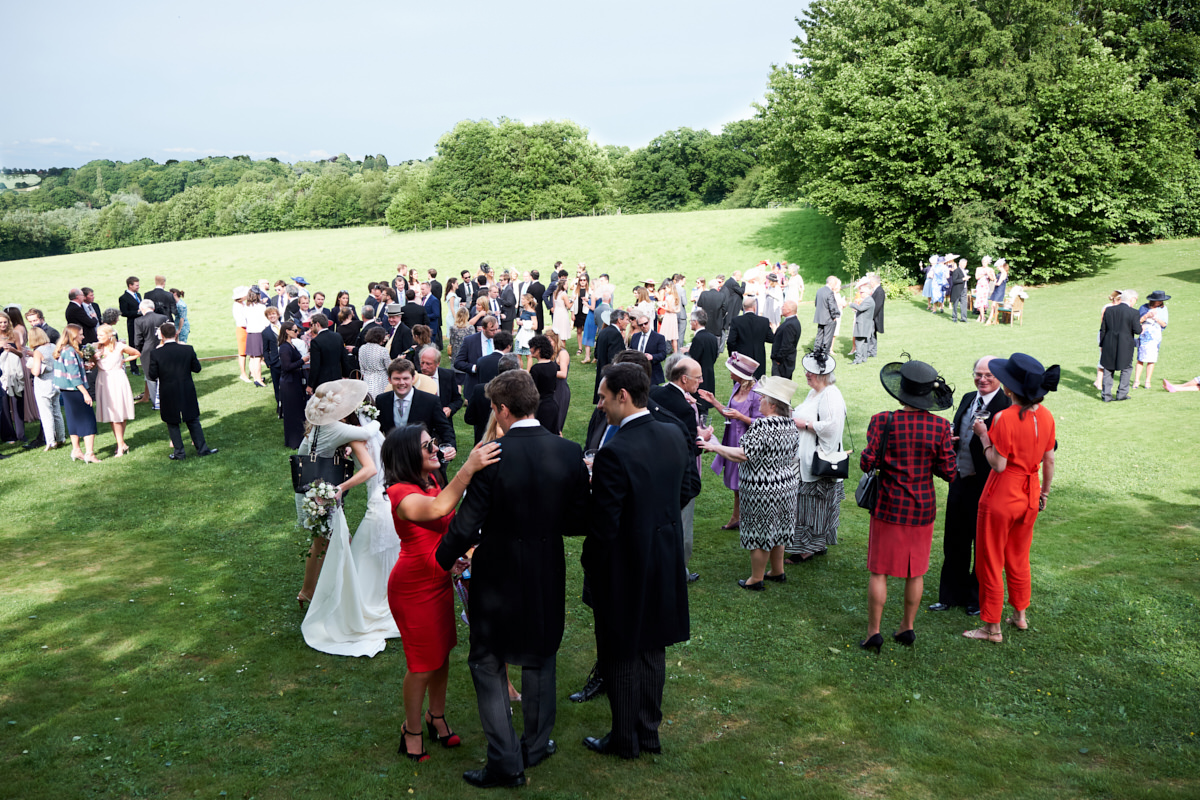 guests at a wedding drink champagne in a field in Sussex
