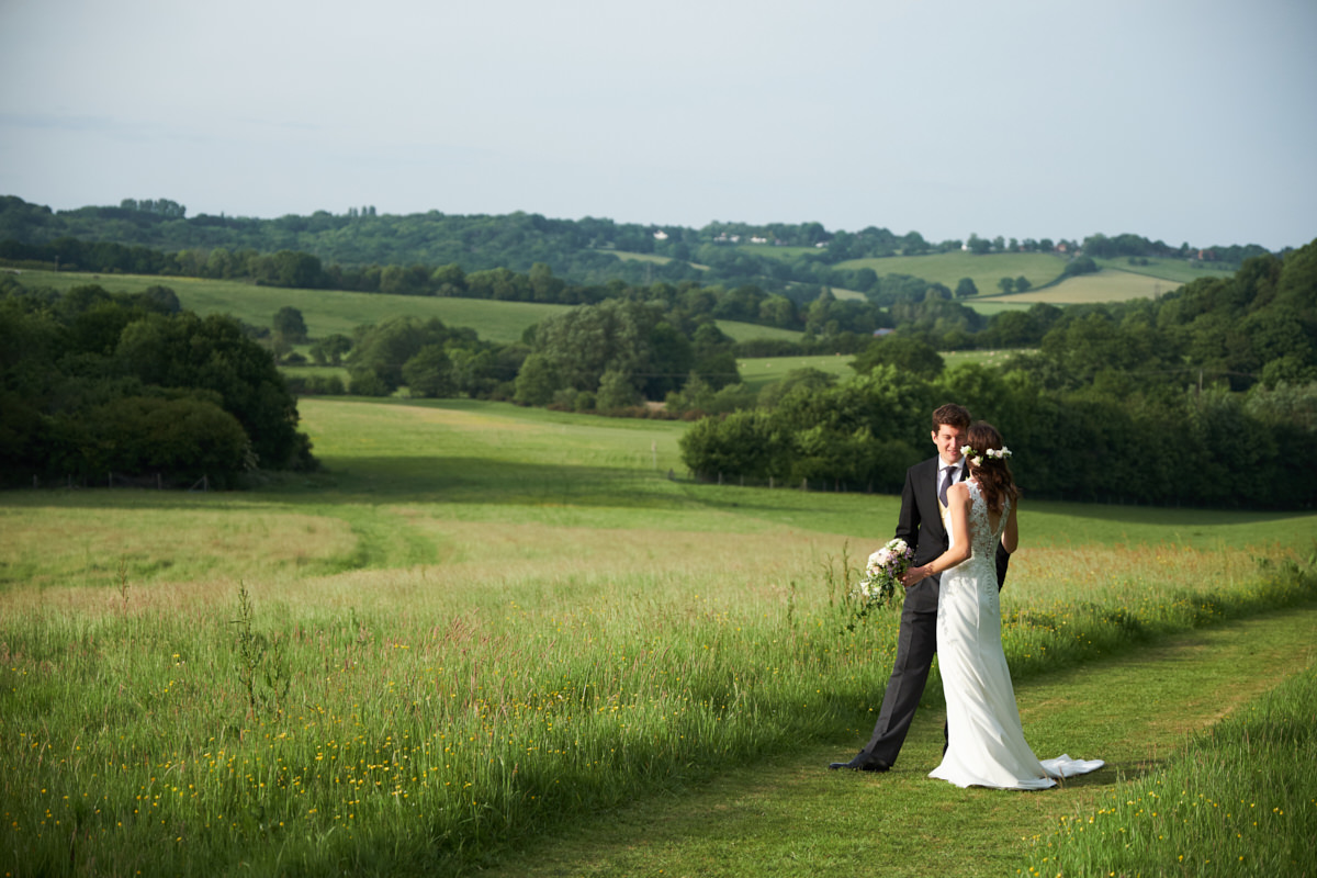 a bride and groom in a field in Sussex waiting to be announced in to their marquee