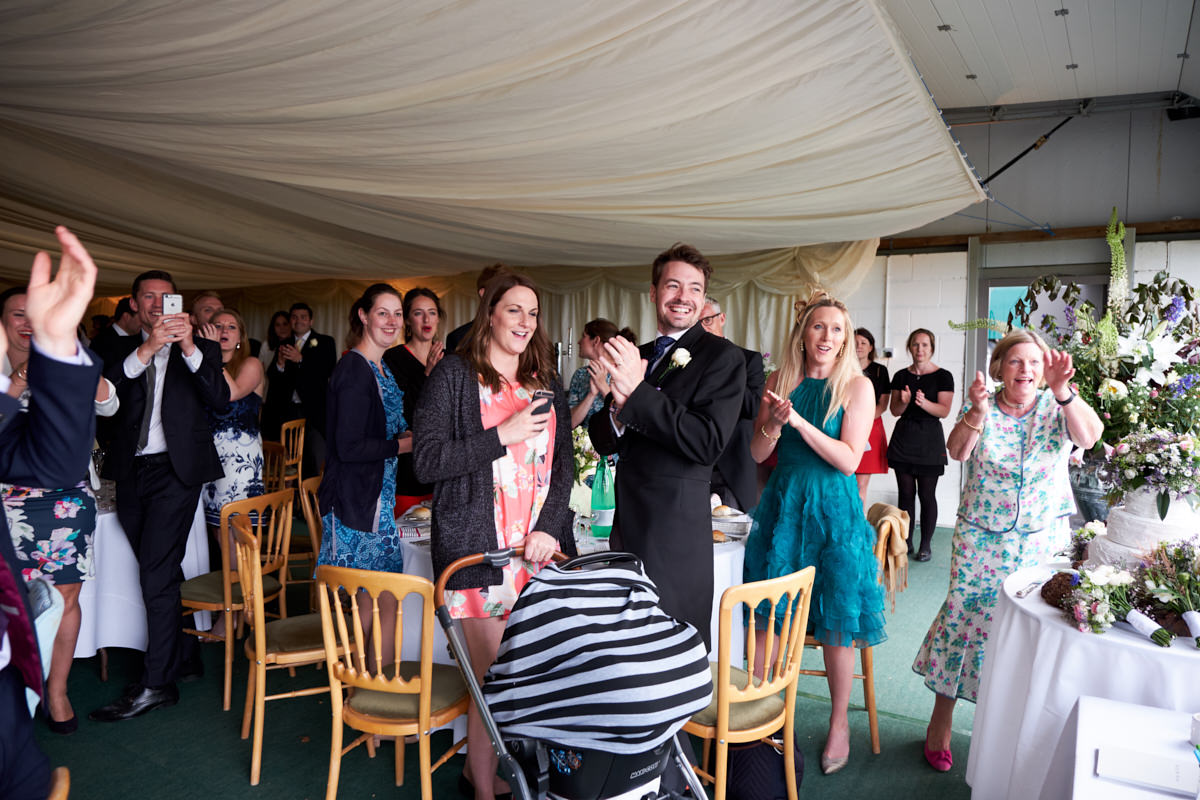 guests applaud the bride and groom as they are announced in to their marquee for the wedding breakfast