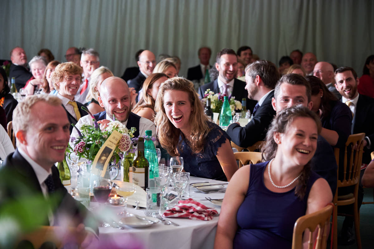 a guest laughing during the speeches in a wedding marquee