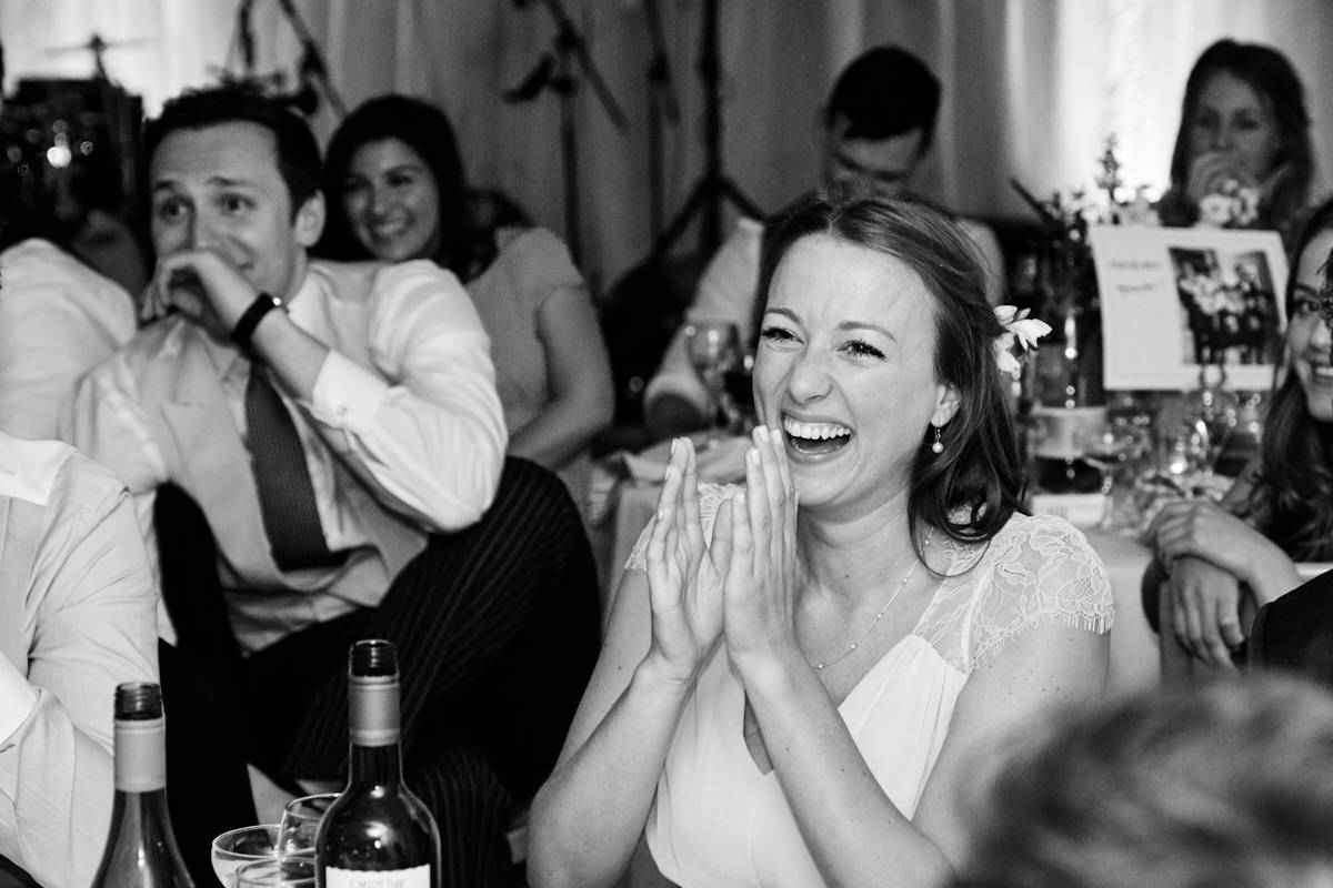 a bridesmaid laughing at the groom's speech