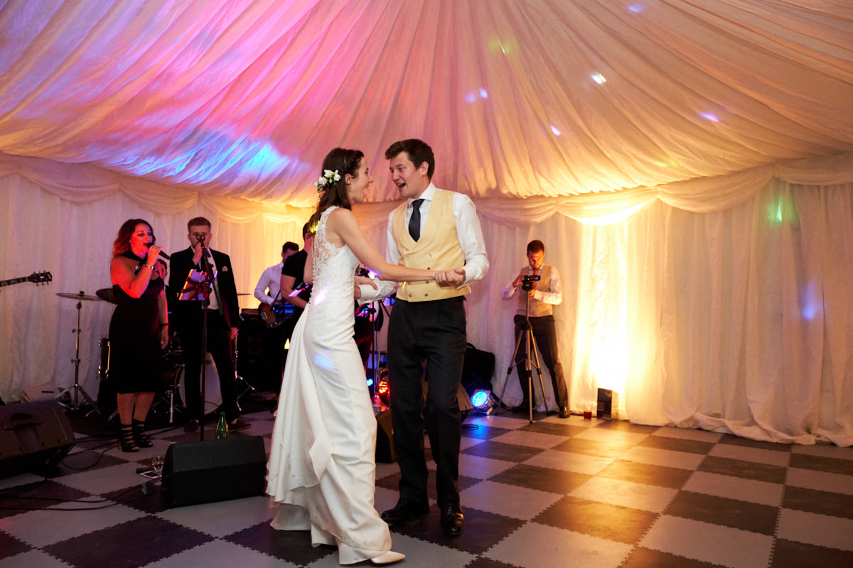 the bride and groom's first dance in their wedding marquee