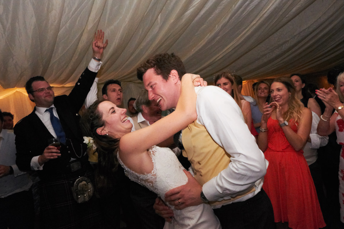 the bride and groom dancing at their marquee wedding
