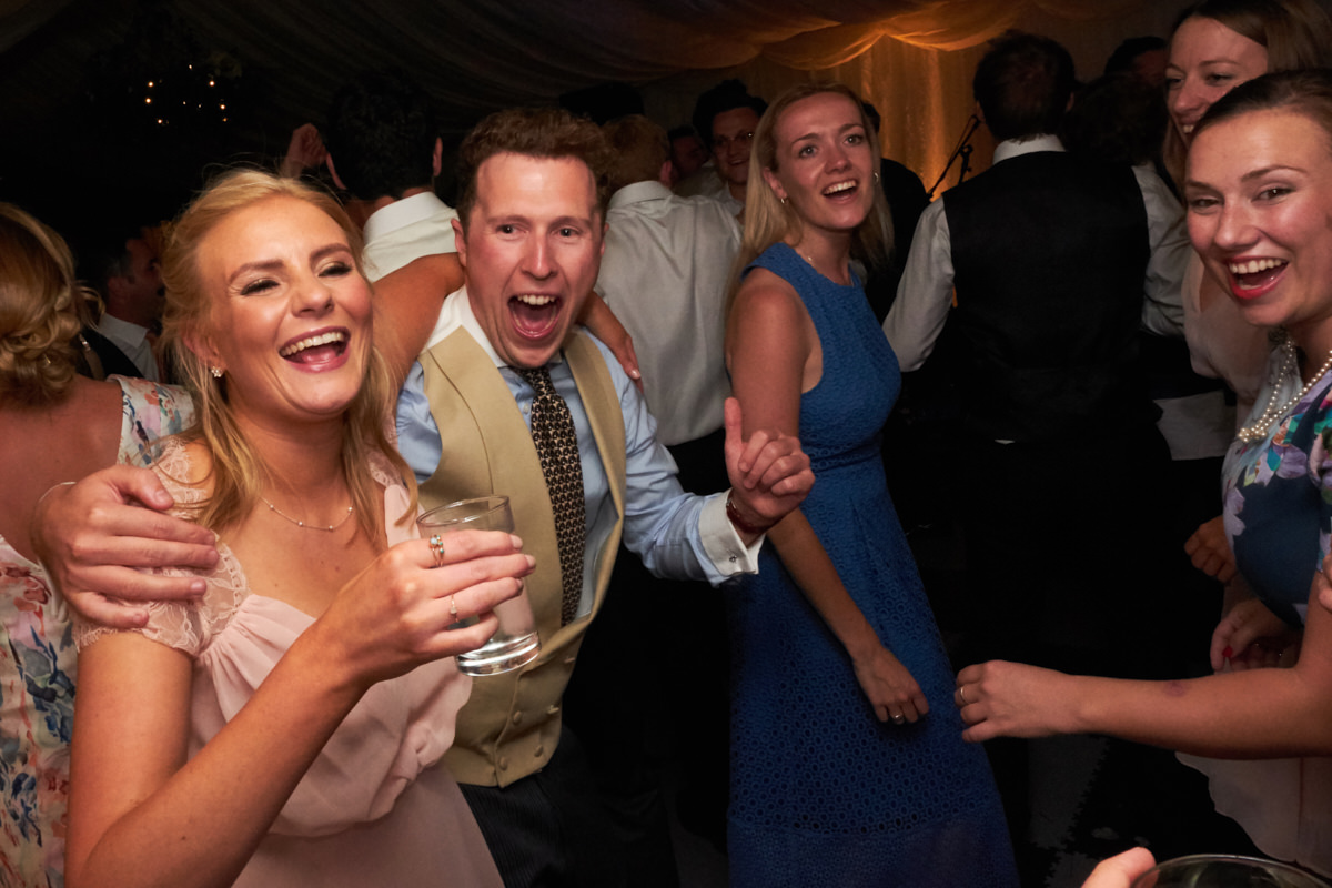 wedding guests cheering and dancing at a marquee wedding in Sussex