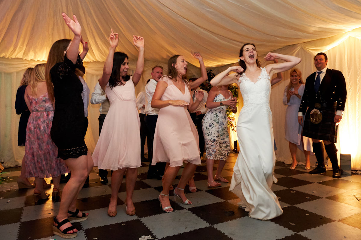 the bride and her bridesmaids doing a dance routine