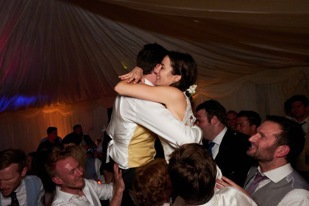 the bride and groom hugging on the dance floor