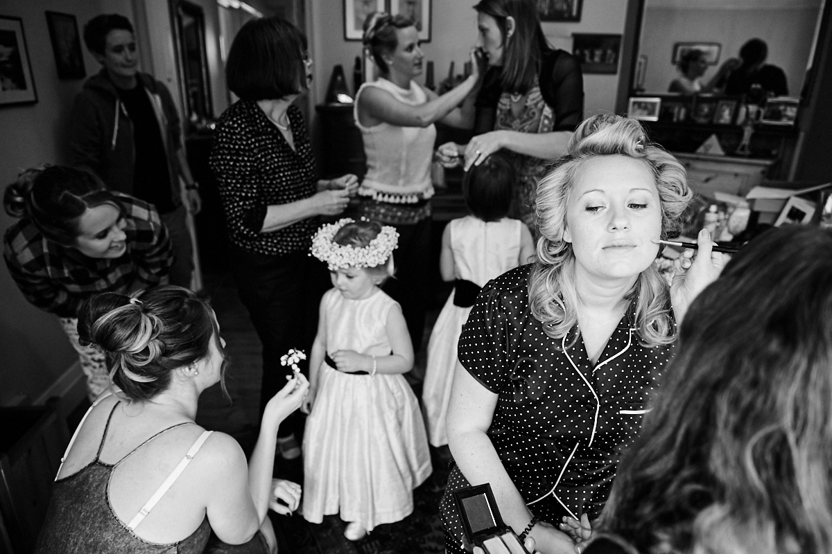 the bride having her makeup done while her bridesmaids talk in the background