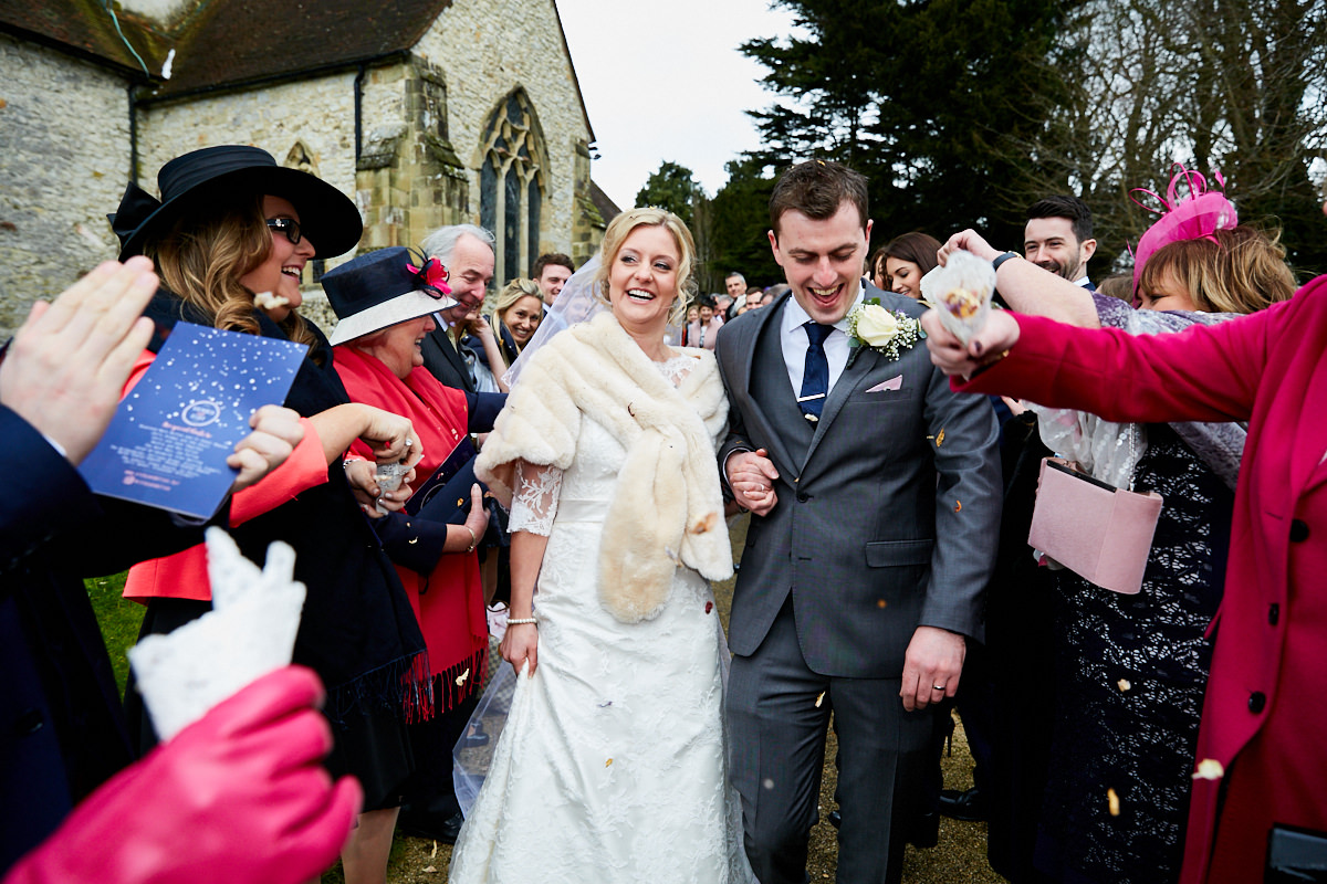 a bride and groom during their confetti run at their Sussex wedding