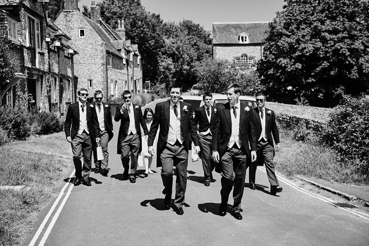 the groom and all his groomsmen walking along the road