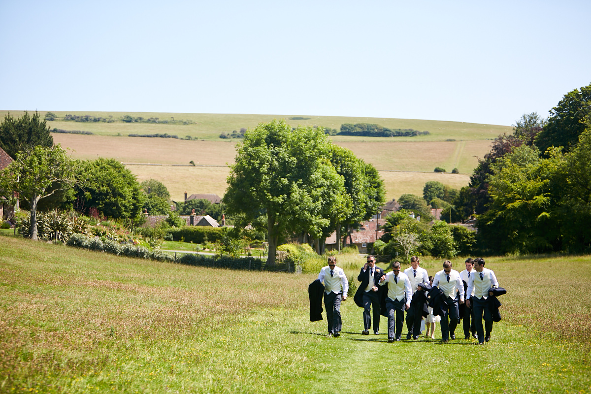 the groom and the groomsmen walking up the hill towards the church