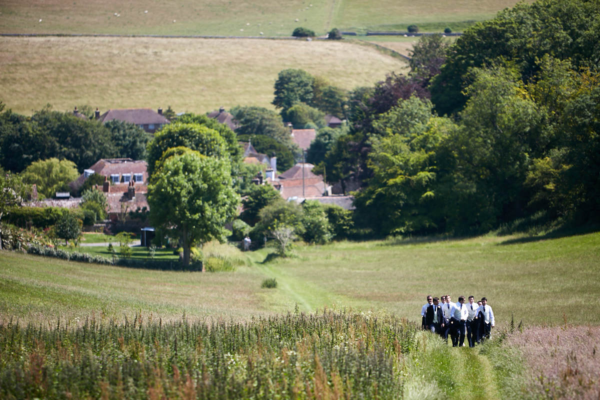 the Sussex countryside with the groom and his groomsmen small in the photo walking up the hill