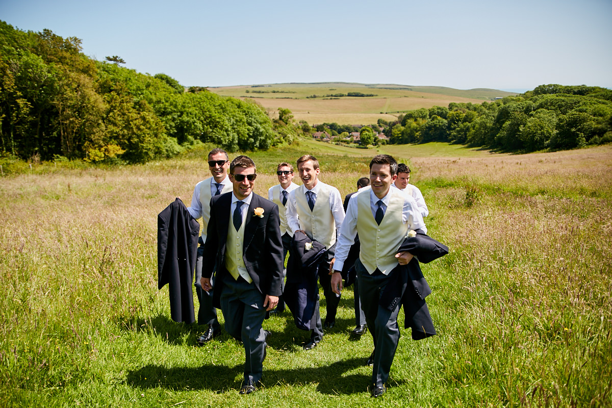 the groom and his groomsmen near the top of the hill on the way to the church