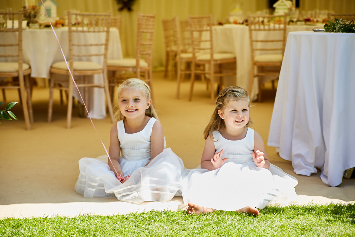 two flower girls playing in the wedding marquee